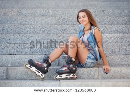 smiling girl wearing jeans vest and shorts sitting on the stairs