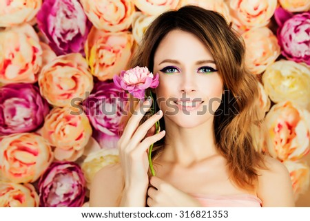 Smiling Girl with Flower on Blossom Background. Woman Fashion Model with Coloring Hairstyle, Manicure and Makeup