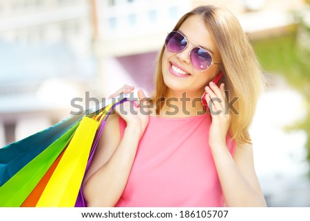 Smiling girl with shopping bags talking on the phone