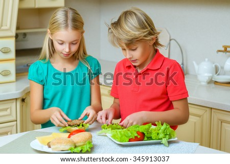 smiling happy boy and girl making homemade hamburgers or sandwiches