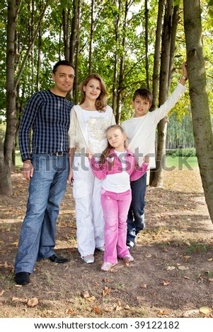 smiling happy family of four in park
