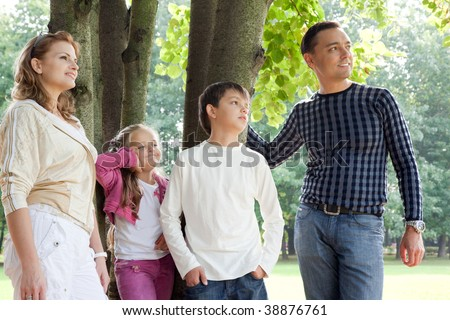 smiling happy family of four looking aside outdoors