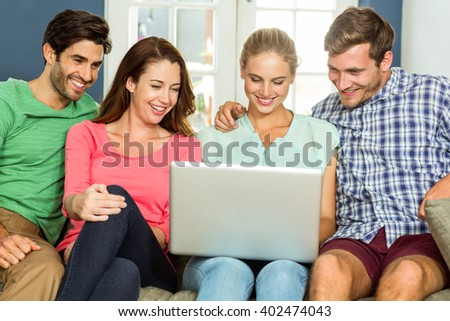 Smiling happy friends using laptop at home