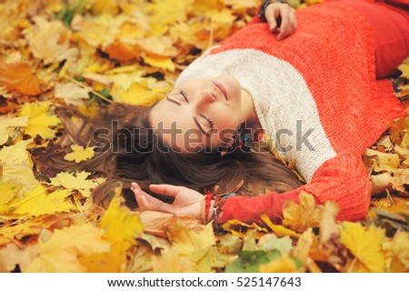 Smiling happy girl portrait, lying in autumn leaves, relax with closed eyes, dressed in fashion sweater, autumn outdoor