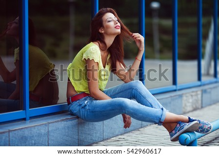 Smiling hipster girl in blue jeans in the summer city. Modern youth lifestyle concept. Outdoor shot