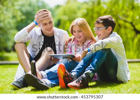 Smiling kids having fun and look to tablet at grass. Children playing outdoors in summer. teenagers communicate outdoor