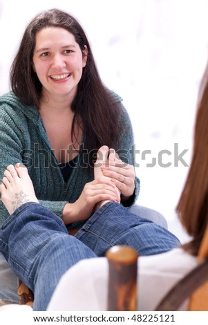 smiling lady giving someone a foot massage