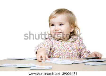Smiling little girl playing with puzzle cards