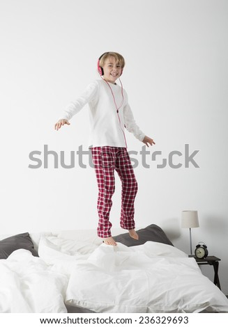 Smiling Little Girl with headphones jumping in bed