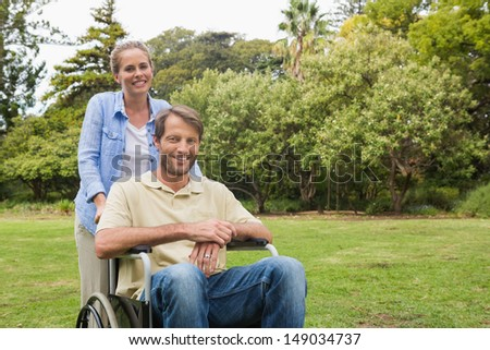 Smiling man in wheelchair with partner looking at camera in a park