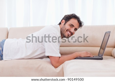 Smiling man using a notebook in his living room
