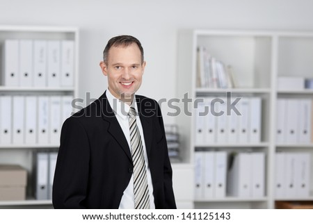 Smiling mature businessman standing over the office files background