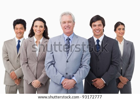 Smiling mature businessman standing with his team against a white background
