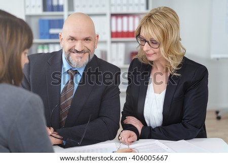 Smiling mature businessman with beard and suit sitting with female co-workers in staff meeting at small office