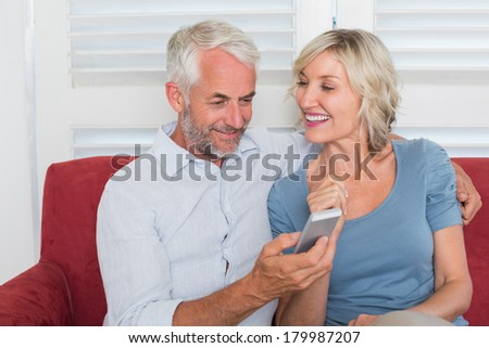 Smiling mature couple reading text message at home
