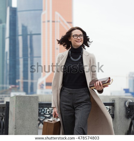 smiling middle aged brunette in a bright coat in the business district of the city. woman with wooden case and books in their hands. fashion