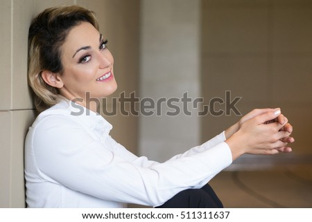 Smiling Middle-aged Businesswoman Sitting on Floor