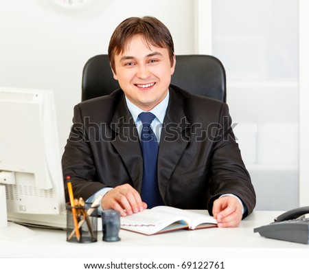 Smiling modern business man sitting at office desk
