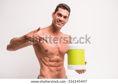 Smiling muscular man with jar of protein. Sports nutrition.