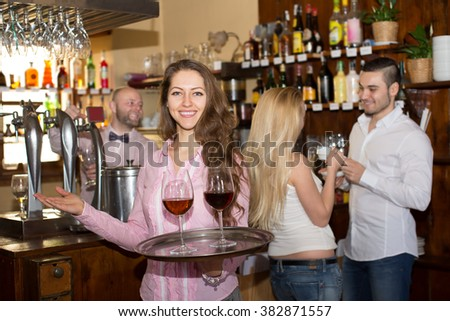 Smiling nippy serving bar guests with a beverages