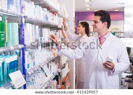 Smiling pharmacist and pharmacy technician posing in drugstore retail