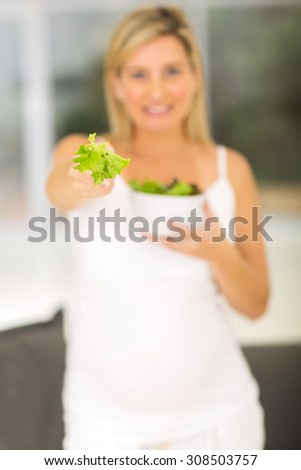 smiling pregnant woman giving fork with green salad
