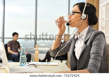 Smiling pretty business woman with headset drinking water in an office environment at foreground. Copyspace