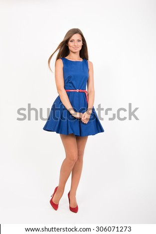 Smiling pretty girl in blue dress, studio full length portrait