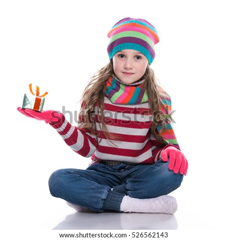 Smiling pretty little girl wearing colorful knitted scarf, hat and gloves, holding christmas gift isolated on white background. Winter clothes.