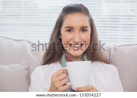 Smiling pretty model holding cup of coffee sitting on cozy sofa
