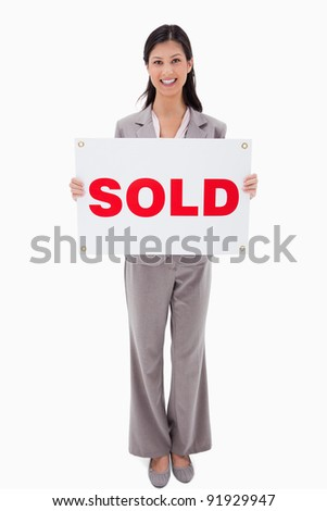 Smiling real estate agent with sold sign against a white background