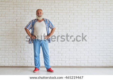 Smiling senior dressed fashionably standing and holding hands on his belt, white brick wall in background