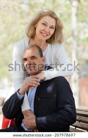 Smiling senior mature couple hugging outdoor in autumn day