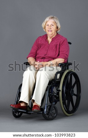 Smiling senior woman seated in a wheelchair, either handicapped or disabled, looking at camera over neutral grey background.