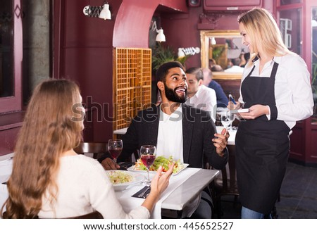 smiling spanish  waitress serving meal for young couple at table