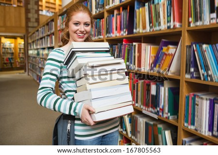 Smiling student holding heavy pile of books standing in library at the university