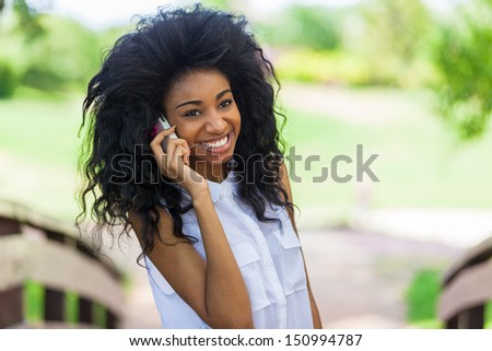 Smiling teenage black girl using a mobile phone  - African people