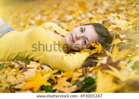 Smiling teenage girl lying on autumn leaves