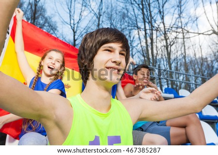Smiling teenage sport supporters watching the game