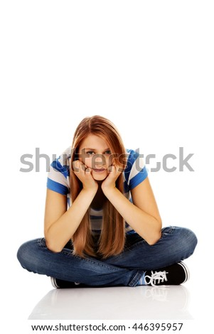 Smiling teenage woman sitting on a floor with legs crossed