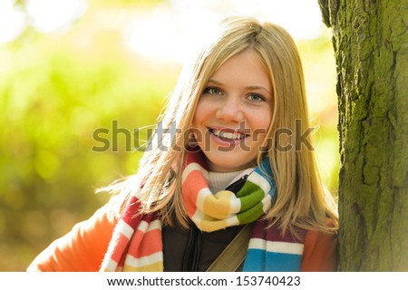 Smiling teenager blonde girl woods tree autumn happy