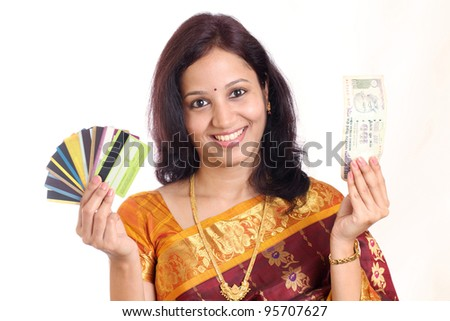 Smiling traditional Indian woman with Indian currency and credit cards