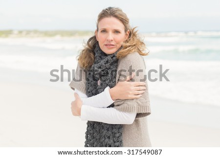 Smiling woman feeling the cold at the beach