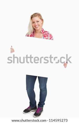 Smiling woman holding a blank placard against a white background