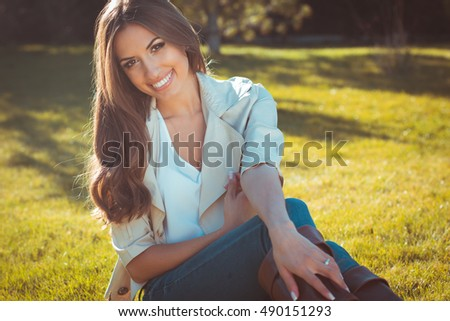 Smiling woman is wearing warm clothes in park