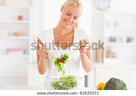 Smiling woman mixing a salad in her kitchen