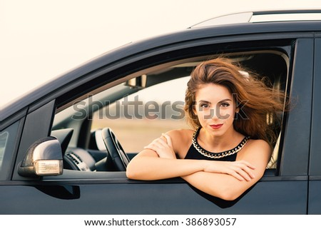 Smiling woman portrait sit in her car. Filtered image.