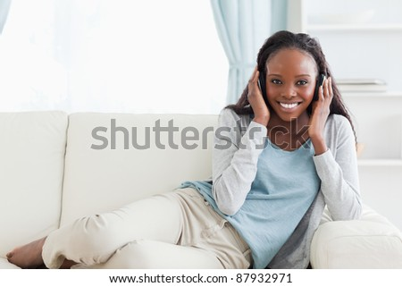 Smiling woman relaxing on sofa with headphones on