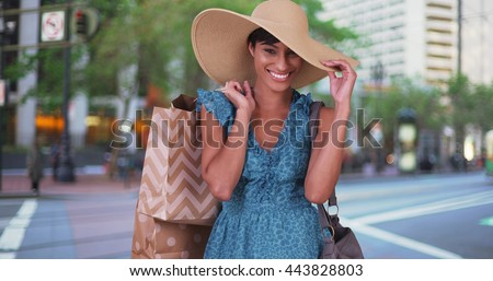 Smiling woman with shopping bags over her shoulder wearing blue sundress and sunhat in San Francisco city