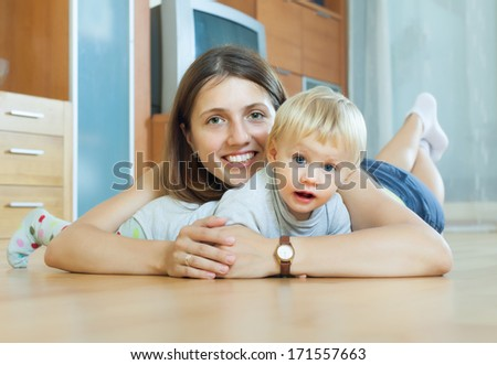 smiling  woman with toddler on  wooden floor in home